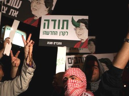 "Im Tirtzu demonstrators, dressed as Hamas terrorists in front of the home of NIF President Naomi Chazan. The sign reads ""thank you, New (Israel) Fund""."