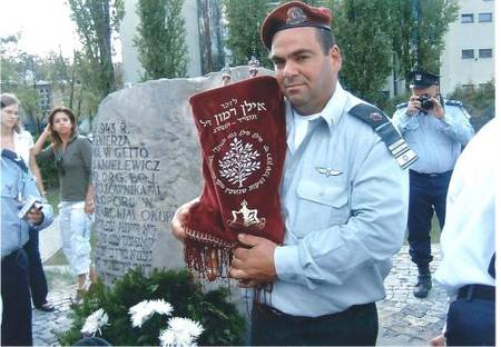 "Lt. Col. Dov Harari, z""l, holding a Sefer Torah written for Ilan Ramon. I believe the setting is Yad Vashem in 2003, when the Torah was dedicated (IDF Spokesperson blog)."