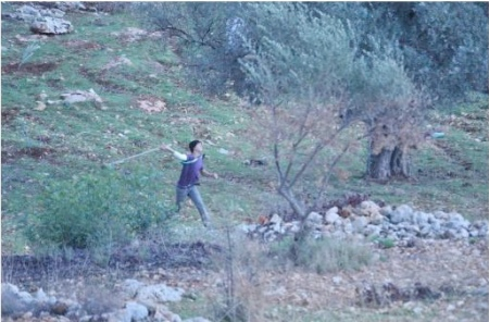 Protester uses sling to throw a rock at security forces in Bili'in Friday. IDF photo.
