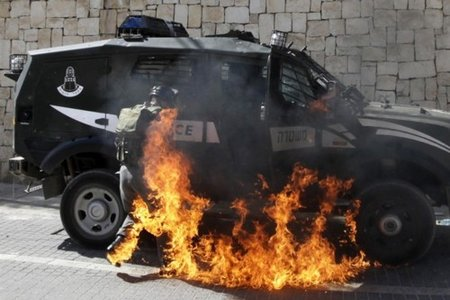 An Israeli border police officer is burned by a firebomb thrown by a 'Palestinian' demonstrator in Jerusalem, March 18. The officer survived.