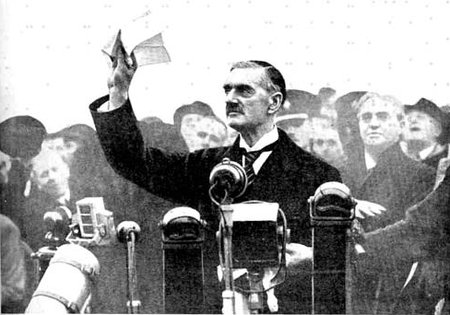 "British PM Neville Chamberlain holds worthless treaty received from Hitler, proclaims ""peace in our time"""
