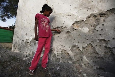 An Israeli girl in Beersheva examines ball bearings embedded in the wall of a school building damaged by a Grad missile fired from Gaza. The school was closed when the rocket landed, and no one was hurt.