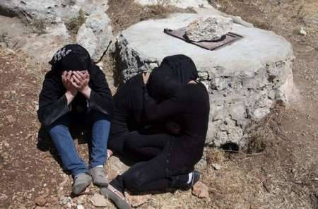 Two sisters of Aya Baradiya cry at the well where Aya was murdered